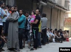 FILE - People queue for bread in the rebel held al-Shaar neighborhood of Aleppo, Syria, July 14, 2016.