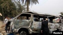 Seorang pria memeriksa sebuah mobil yang hancur dibom di Baghdad, Minggu, 16 Februari 2014.