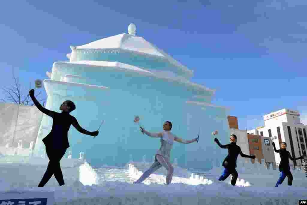 Bailarinas taiwaneses actúan frente a una gran escultura de nieve del monumento a Chiang Kai-shek en el festival de la nieve en Sapporo, Japón.