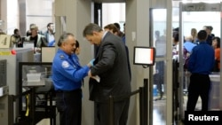 FILE An airline passenger is patted down by a TSA agent after passing through a full-body scanner at Los Angeles International Airport in Los Angeles, California, Feb. 20, 2014. The TSA is under fire as waiting periods for passenger screenings grow.