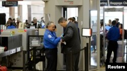 FILE - An airline passenger is patted down by a TSA agent after passing through a full-body scanner at Los Angeles International Airport in Los Angeles, California, Feb. 20, 2014.
