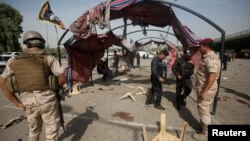 Iraq security forces gather at the site of a suicide bomb attack in Baghdad, Iraq, Oct, 16, 2016.