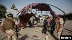 이라크 보안군이 15일 자살폭탄테러가 발생한 바그다드 현장에 모여 피해 상황을 살피고 있다.