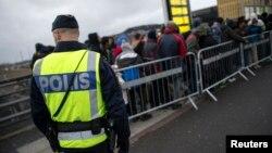 Arhiva - Švedski policajac posmatra dok migranti doazle na stanicu Hajlie u predgrađu Malmea, Švedska.