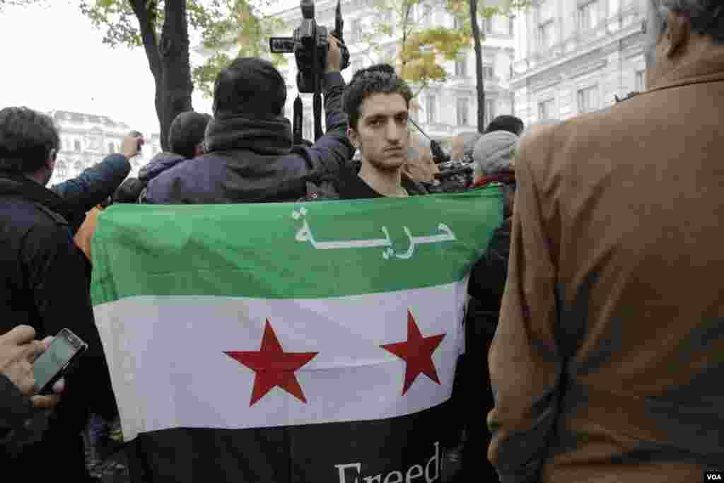 جوان سوری مخالف دولت بشار اسد همزمان با برگزاری نشست صلح سوریه در وین، در تجمعی پرچم مخالفان را در دست گرفته که روی آن نوشته شده: آزادی.