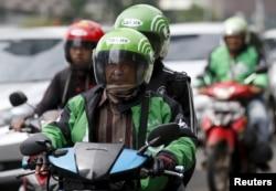 Seorang pengemudi dan penumpang naik sepeda motor, bagian dari layanan naik-naik Go-Jek, di jalan yang sibuk di Jakarta Pusat, 18 Desember 2015. (Foto: Reuters)