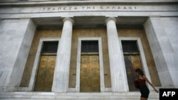 Перехожа поблизу Центрального банку Греції в Афінах. Вартість нових запозичень для обтяженої неймовірною кількістю боргів Греції постійно збільшується. Тим часом уряду не вдається прискорити впровадження необхідних реформ.