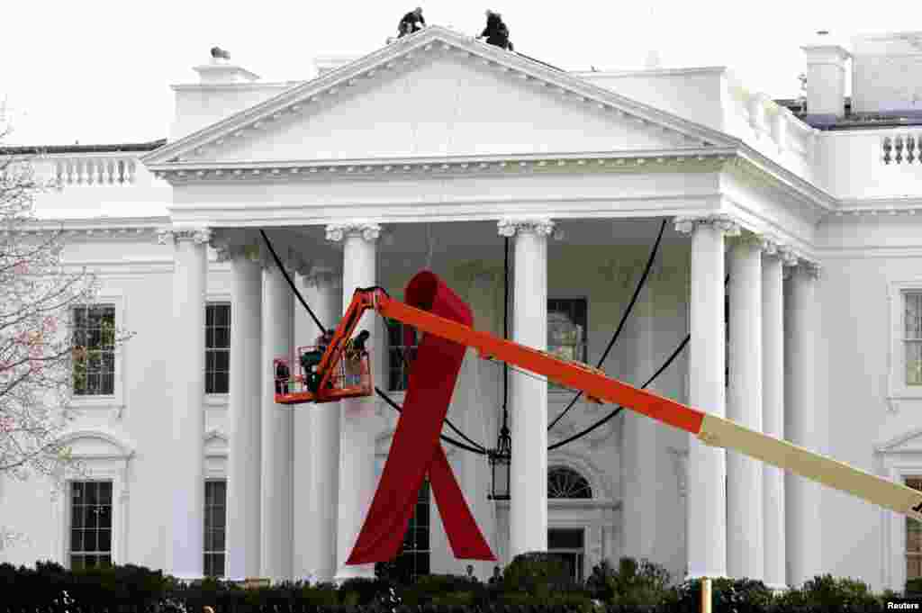 A large red ribbon is installed on the North Portico of the White House in Washington, November 30, 2012.