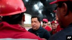 El presidente venezolano Hugo Chávez conversa con trabajadores de PDVSA mientras la refinería de Amuay arde todavía en el fondo, el domingo 26 de agosto de 2012.