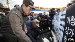 Veteran Angkatan Darat Korea Selatan meletakkan bunga di depan spanduk bergambar penjaga pantai Lee Cheong-ho saat protes anti-Tiongkok depan Kedutaan Tiongkok diSeoul (13/12).