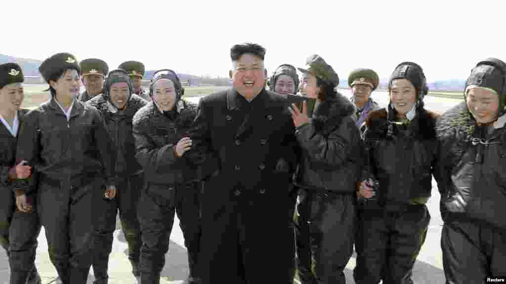 Nhà lãnh đạo Bắc Triều Tiên Kim Jong Un gặp gỡ các nữ phi công sau khi theo dõi cuộc lập trận của đơn vị không quân và phòng không 2620, ngày 7/3/2014.