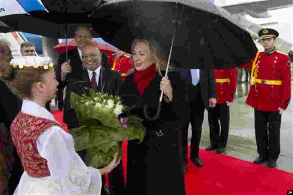 US Secretary of State Hillary Clinton receives flowers upon arrival at Tirana Rinas Airport in Tirana, Thursday, Nov. 1, 2012. Hillary Clinton arrived in EU-hopeful Albania on the last leg of her Balkans tour where she is expected to urge opposing politic