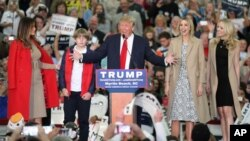 Republican presidential candidate Donald Trump , center, speaks with, from left, his wife, Melania, left, son Baron, and daughters Ivanka and Tiffany during a campaign rally in Myrtle Beach, South Carolina, Nov. 24, 2015.