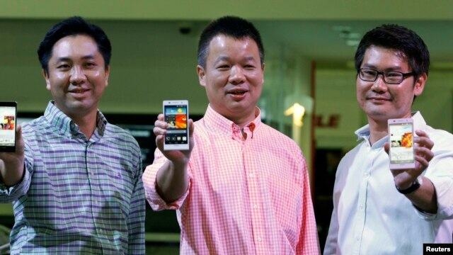 Huawei's Singapore CEO Zhou Bin (L-R), David Wei, President of Huawei South Pacific and Lim Chee Siong Chief Marketing Officer, Huawei South Pacific, show the new Huawei Ascend P6 Android-based smartphones during their launch at CommunicAsia communication