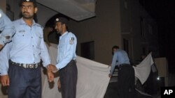 Polisi Pakistan menutup kendaraan yang membawa keluarga Bin Laden dari pandangan media, di Islamabad, Kamis (26/4).