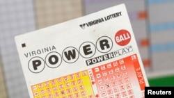 Seorang pria memegang tiket lotre Virginia dengan hadian $400 juta di Arlington, Virginia, 19 February 2014.
