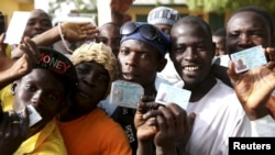 Men holds ID cards as they wait in line to register to vote in a polling station during elections in Kano, March 28, 2015.