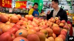 2018年3月23日,在北京一家超市,一位身穿带有美国食品公司标志的制服的女子帮助一位顾客购买苹果。