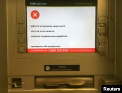 "FILE - A screen of an idle virus affected cash machine in a state-run OshchadBank says ""Sorry for inconvenience/Under repair"" in Kiev, Ukraine, June 28, 2017."
