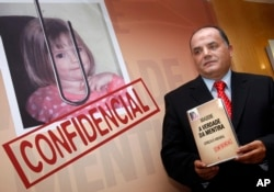 "FILE- Former detective Goncalo Amaral poses with his book, July 24, 2008, whose title translates as ""The Truth in the Lies,"" during its launch in Lisbon. Amaral says in the book he is convinced that Madeleine McCann died in the vacation apartment from where she went missing."