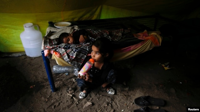A Pakistani Christian girl drinks milk as her brother sleeps, in a tent provided for Christian families whose homes were set on fire by a mob, in Badami Bagh, Lahore, Pakistan, March 13, 2013.