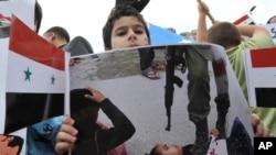 一名敘利亞兒童手持國旗和圖片﹐抗議敘利亞軍隊粗暴對待兒童。