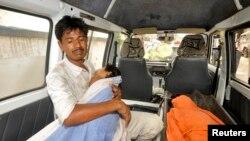 Seorang pria memangku anaknya yang sakit setelah makan siang gratis di sebelah timur kota Patna, India (17/7).