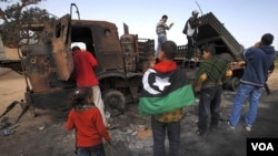 Residentes observan un lanzamisiles de las fuerzas pro Gadhafi, destruido por un ataques de los aviones de las fuerzas internacionales en la ruta entre Benghazi y Ajdabiyah.