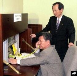 Menteri Unifikasi Korea Selatan Park Jae-kyu mengamati seorang petugas penghubung Korea Selatan, Oh Sei-eung saat mencoba menelepon pihak Korea Utara, saat dibukanya kembali kantor penghubung Selatan-Utara di desa perbatasan Panmunjom, 3 Januari 2018.