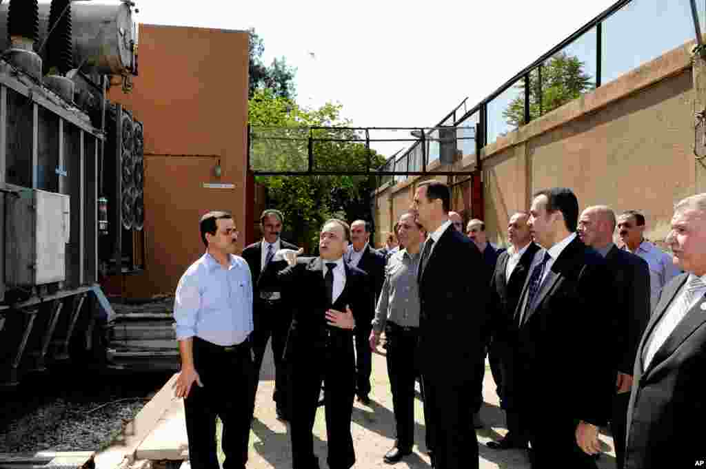 This photo released by the Syrian official news agency SANA shows Syrian President Bashar al-Assad visiting the Umayyad Electrical Station, Damascus, Syria, May 1, 2013.