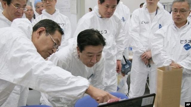 Japan's Prime Minister Yoshihiko Noda (C) listens to Masao Yoshida, director of the Fukushima Daiichi nuclear power plant, while visiting the crippled plant in Fukushima prefecture, September 8, 2011.