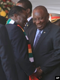 FILE: Zimbabwean President Emmerson Mnangagwa talks with South African President Cyrill Ramaphosa, right, during his inauguration ceremony at the National Sports Stadium in Harare, Sunday, Aug. 26, 2018.