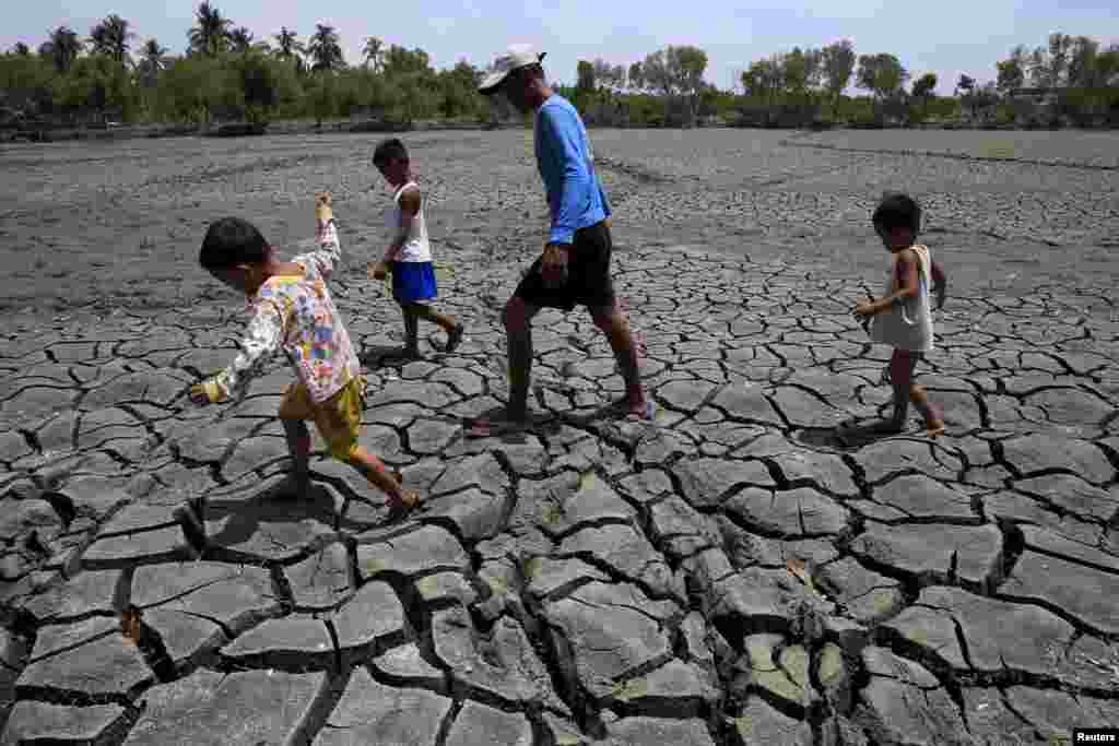 A father and his children walk over the cracked soil of a 1.5 hectare dried up area in the Novaleta town in Cavite province, south of Manila, the Philippines.