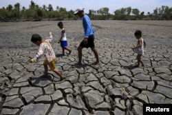 A father with his children walk over the cracked soil of a 1.5 hectare dried up fishery at the Novaleta town in Cavite province, south of Manila May 26, 2015. President Benigno Aquino III approved the proposal of the National Food Authority (NFA) to impor
