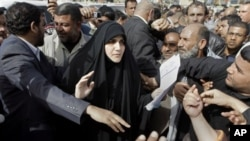 Maha al-Dori, a lawmaker loyal to anti-American Shiite cleric Muqtada al-Sadr, collects the demands of protesters during a protest at Tahrir Square in Baghdad, Iraq, February 23, 2011