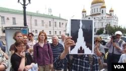导游帕维尔手举苏维埃大厦和列宁像方案,后面是苏联解体后新建的救世主大教堂。(美国之音白桦拍摄)
