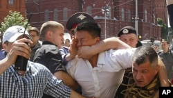 Policemen, some dressed in plain clothes, detain gay rights activist Daniel Choi, center, near the Kremlin during an unsanctioned gay pride parade in central Moscow, May 28, 2011