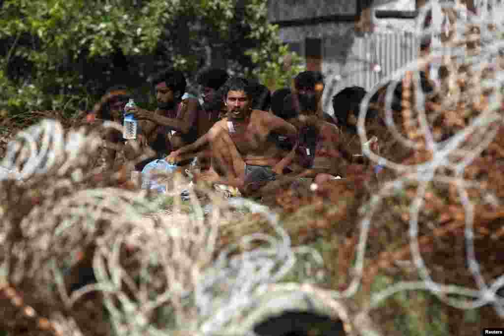 Para migran yang ditemukan di kapal di atas laut, duduk dkeat dermaga Kanyin Chaung setelah mendarat di luar kota Maungdaw, negara bagian Rakhine utara, Myanmar. Para migran ditemukan hanyut di Laut Andaman di kapal nelayan yang terlalu penuh.