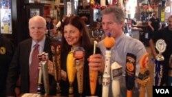 Senatorlar Con Makkeyn, Kelli Ayott və namizəd Skott Braun barda müştərilərə pivə süzürlər.