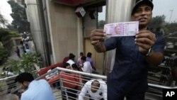 یکتن از شهروندان دهلی جدید با یک بانک نوت ۱۰۰۰ روپیه گی