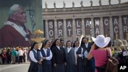 信眾星期五在聖彼得廣場附近的一幅教宗保羅二世畫像前留影