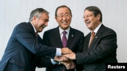FILE - U.N. Secretary-General Ban Ki-moon, center, poses for photographers with Turkish Cypriot leader Mustafa Akinci, left, and Cypriot President Nicos Anastasiades during the Cyprus reunification talks in the Swiss mountain resort of Mont Pelerin, Switzerland, Nov. 7, 2016.