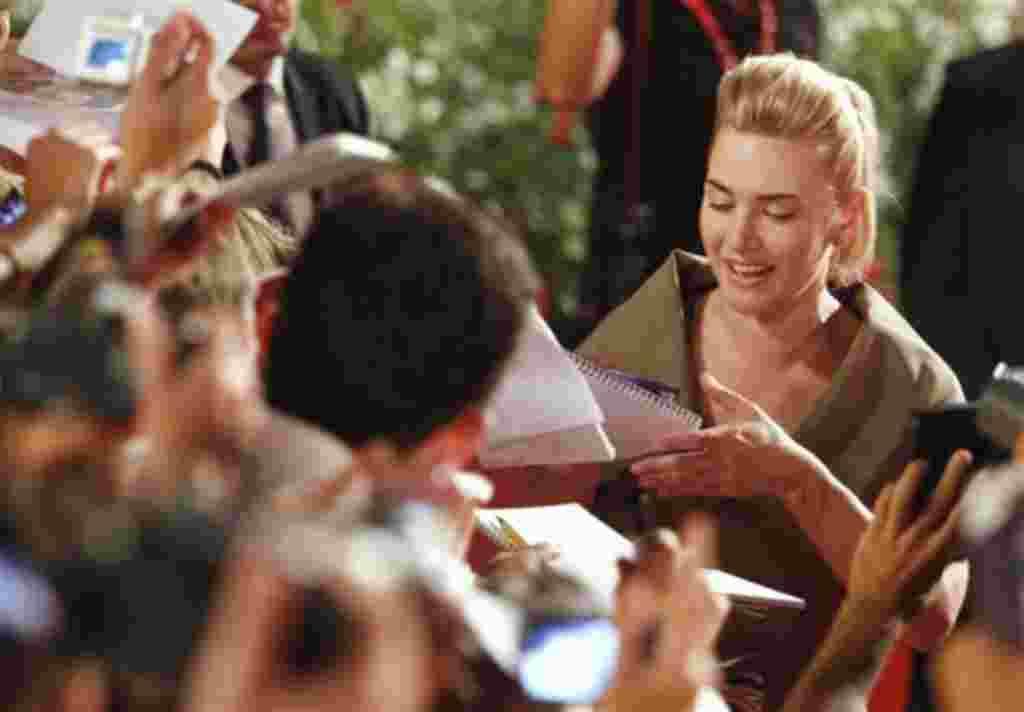 La actriz británica Kate Winslet firma autógrafos a su llegada a la alfombra roja para el estreno de 'Carnicería' en la edición 68 del Festival de Cine de Venecia en Italia,