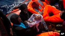 Une femme porte son bébé dans un canot transportant des migrantes venues du Nigeria secourues sur la Méditerranée, à environ 17 miles au nord de Sabratha, Libye, 28 août 2016.