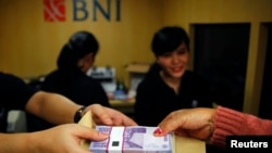 Transaksi keuangan di Bank Negara Indonesia (BNI) di Jakarta (15/7/2013). BNI Merupakan salah satu dari delapan bank yang menyalurkan Kredit Usaha Rakyat untuk meringankan beban UKM.