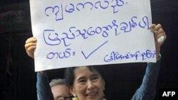 Аун Сан Су Чжи показывает плакат «Я люблю людей»