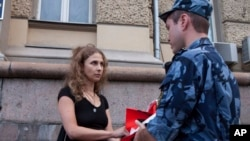 Maria Alekhina, a Russian activist of the feminist protest group Pussy Riot, talks to a policeman as she holds a protest against torture in front of the Federal Penitentiary in Moscow, Russia, Aug. 7, 2018.