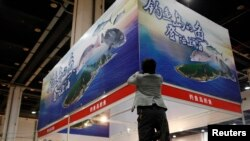 FILE - A vendor installs a poster above his booth, which sells fishes caught by Zhejiang fishermen in waters near disputed islands, known as Diaoyu in China and Senkaku in Japan, during a food exhibition in Shanghai.