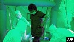 Nhân viên y tế sử dụng máy đếm Geiger để đo cường độ bức xạ cho một phụ nữ vừa được di tản từ khu vực gần nhà máy điện hạt nhân Fukushima Daiichi