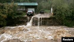 Una casa y un carro corren peligro de ser arrastrados por el agua de la quebrada Coal cerca de Golden, en Colorado.